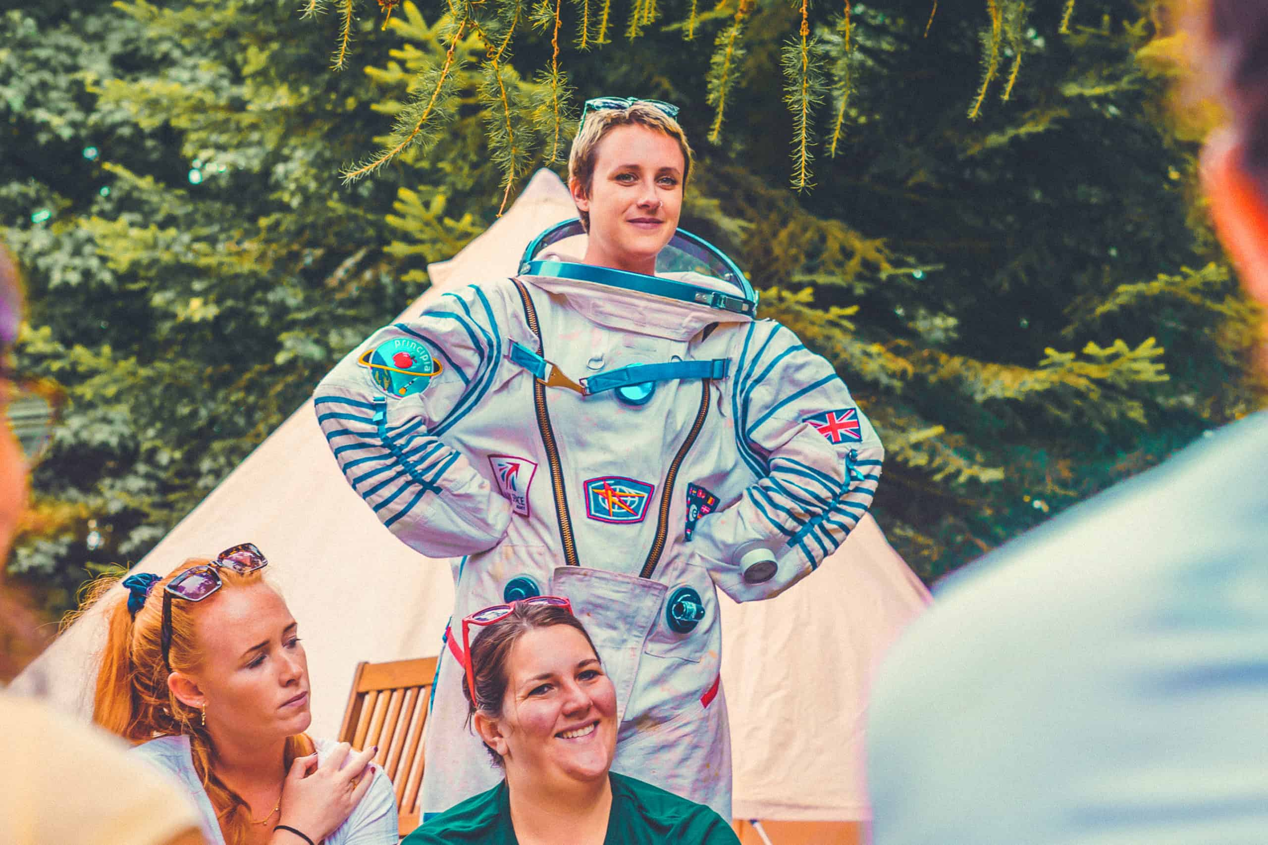 A girl in an astronaut costume learning about astronomy at Camp Wildfire. The UK's Best Alternative Festival. UK's Top Unique Event. A summer weekend break in a forest near London and Kent. An outdoor woodland retreat featuring adventure activities, live music, DJs, parties and camping. Half summer adventure activity camp, half music festival, for adults only.