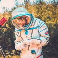 Man dressed as an astronaut with a telescope at the space science activity at Camp Wildfire. A summer weekend break in a forest near London and Kent. An outdoor woodland retreat featuring adventure activities, live music, DJs, parties and camping. Half summer adventure activity camp, half music festival, for adults only.