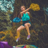 Girl trampolining whilst cheerleading with pom poms at Camp Wildfire. The UK's Best Alternative Festival. UK's Top Unique Event. A summer weekend break in a forest near London and Kent. An outdoor woodland retreat featuring adventure activities, live music, DJs, parties and camping. Half summer adventure activity camp, half music festival, for adults only.