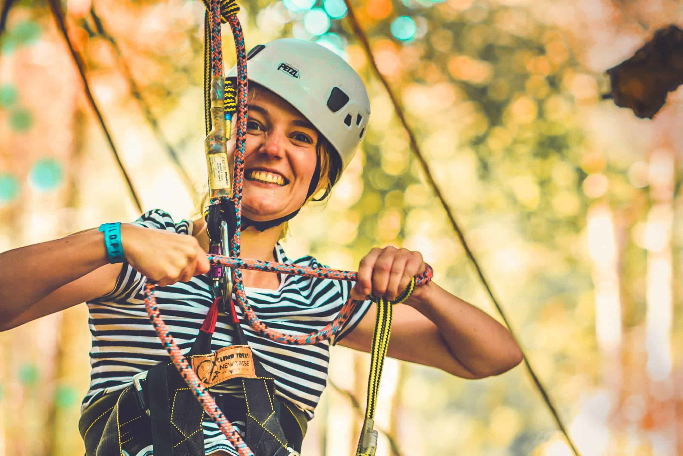 Girl with helmet and ropes on ready to go tree climbing at Camp Wildfire. The UK's Best Alternative Festival. UK's Top Unique Event. A summer weekend break in a forest near London and Kent. An outdoor woodland retreat featuring adventure activities, live music, DJs, parties and camping. Half summer adventure activity camp, half music festival, for adults only.
