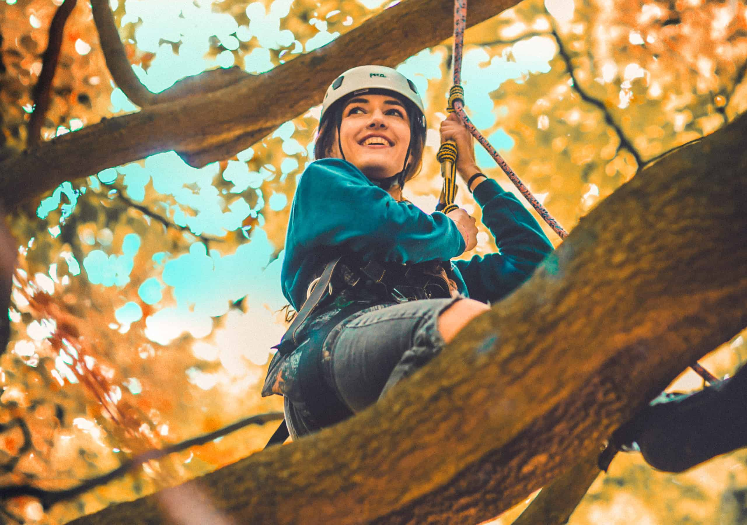 Girl wearing helmet climbing trees at Camp Wildfire. The UK's Best Alternative Festival. UK's Top Unique Event. A summer weekend break in a forest near London and Kent. An outdoor woodland retreat featuring adventure activities, live music, DJs, parties and camping. Half summer adventure activity camp, half music festival, for adults only.