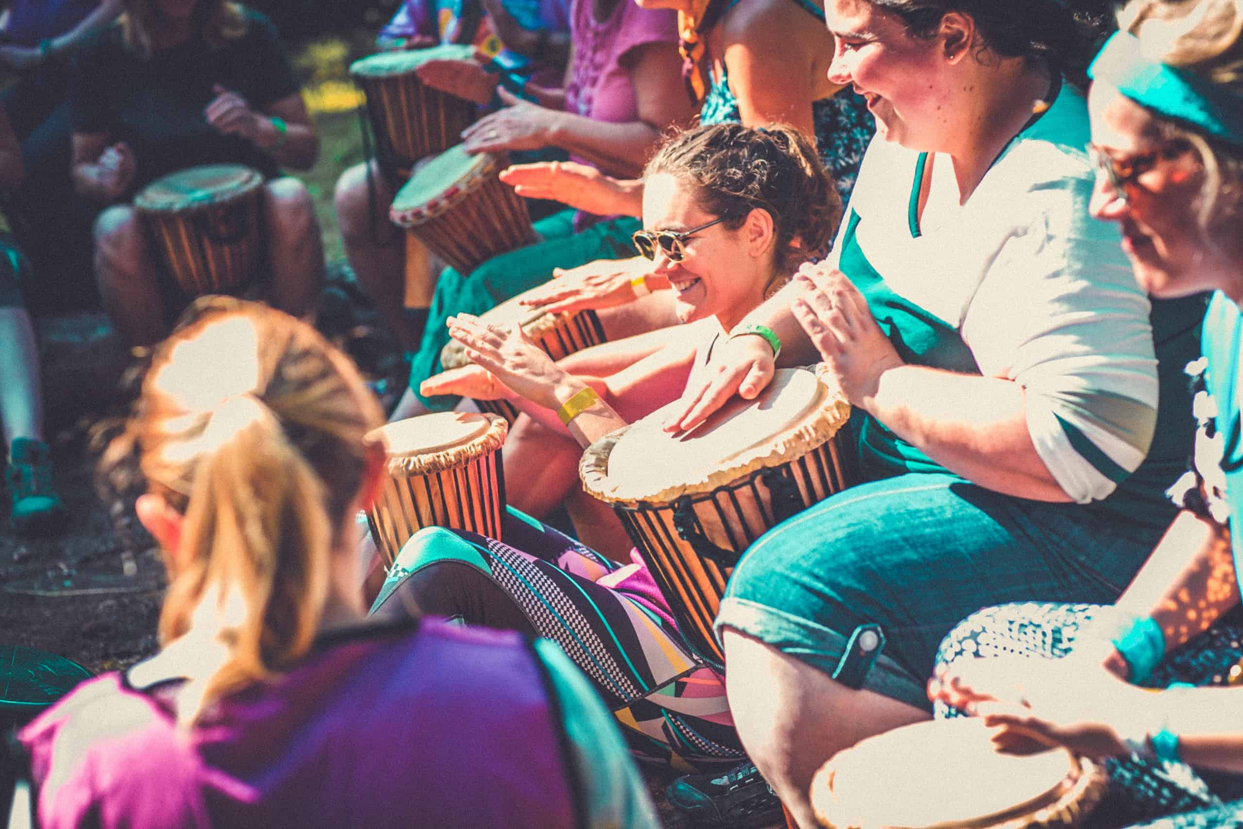People enjoying the tribal drumming activity at Camp Wildfire. A summer weekend break in a forest near London and Kent. An outdoor woodland retreat featuring adventure activities, live music, DJs, parties and camping. Half summer adventure activity camp, half music festival, for adults only.