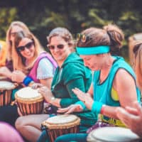 Woman practising tribal drumming at Camp Wildfire. A summer weekend break in a forest near London and Kent. An outdoor woodland retreat featuring adventure activities, live music, DJs, parties and camping. Half summer adventure activity camp, half music festival, for adults only.