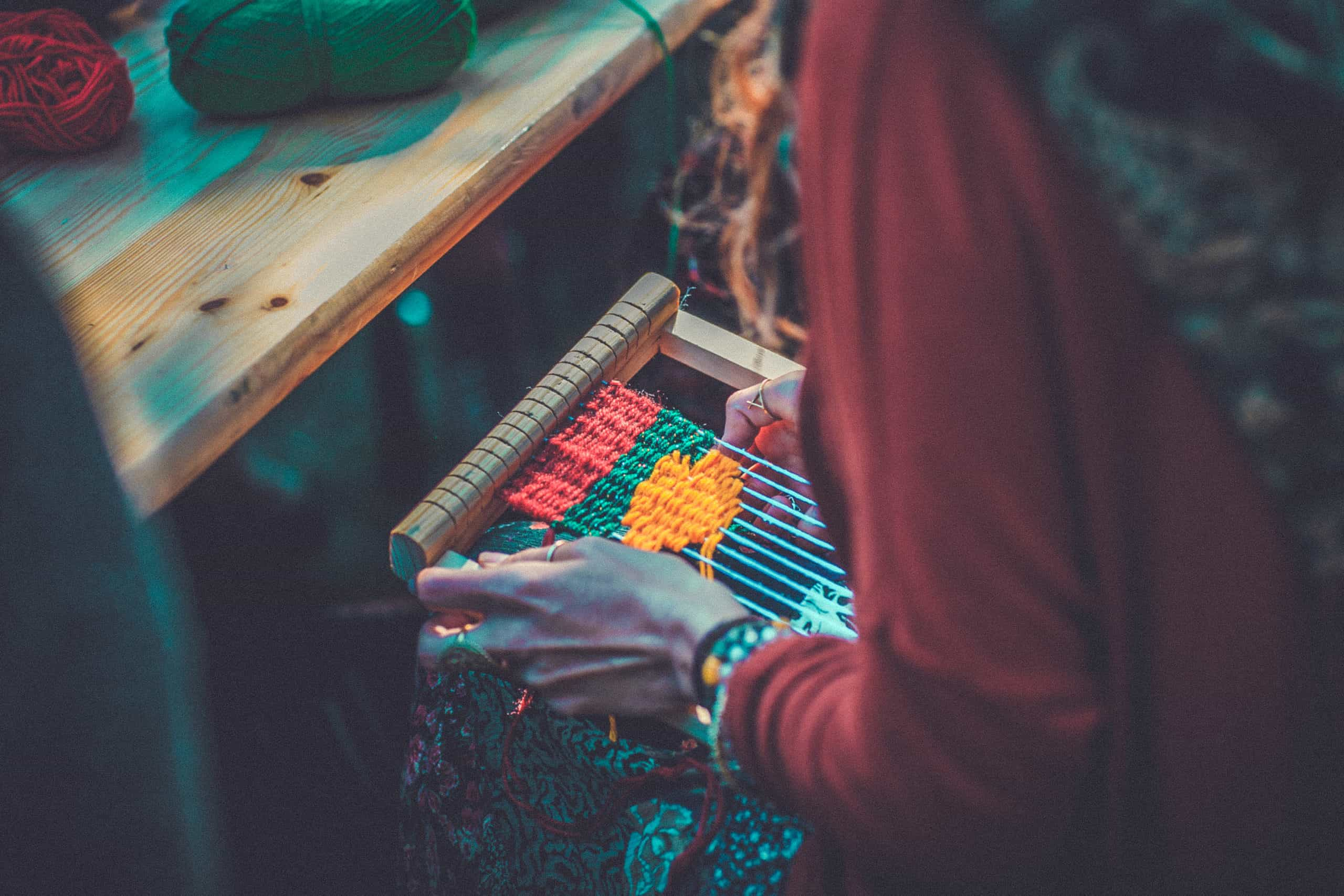 Close up of someone weaving at Camp Wildfire. A summer weekend break in a forest near London and Kent. An outdoor woodland retreat featuring adventure activities, live music, DJs, parties and camping. Half summer adventure activity camp, half music festival, for adults only.
