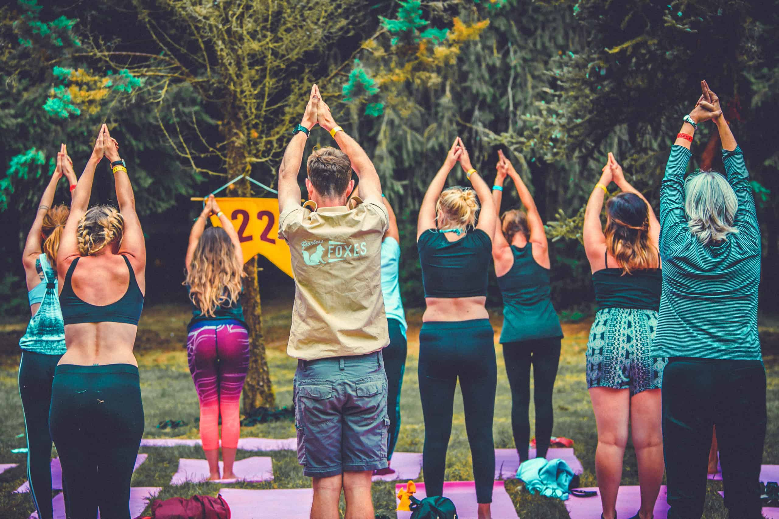 Group of people doing yoga outside at Camp Wildfire. The UK's Best Alternative Festival. UK's Top Unique Event. A summer weekend break in a forest near London and Kent. An outdoor woodland retreat featuring adventure activities, live music, DJs, parties and camping. Half summer adventure activity camp, half music festival, for adults only.