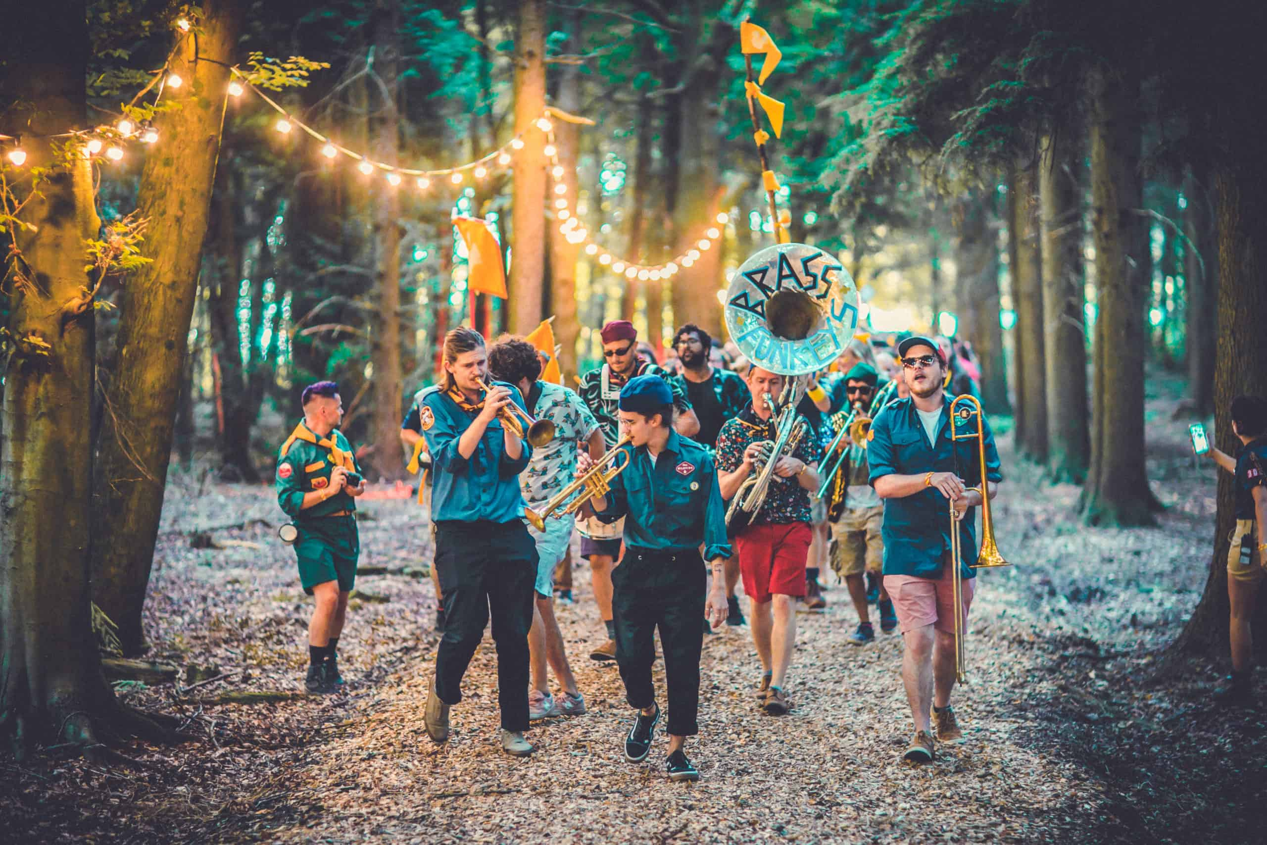 Adventurers in patrol uniforms with instruments marching in the Camp Wildfire parade. A summer weekend break in a forest near London and Kent. An outdoor woodland retreat featuring adventure activities, live music, DJs, parties and camping. Half summer adventure activity camp, half music festival, for adults only.