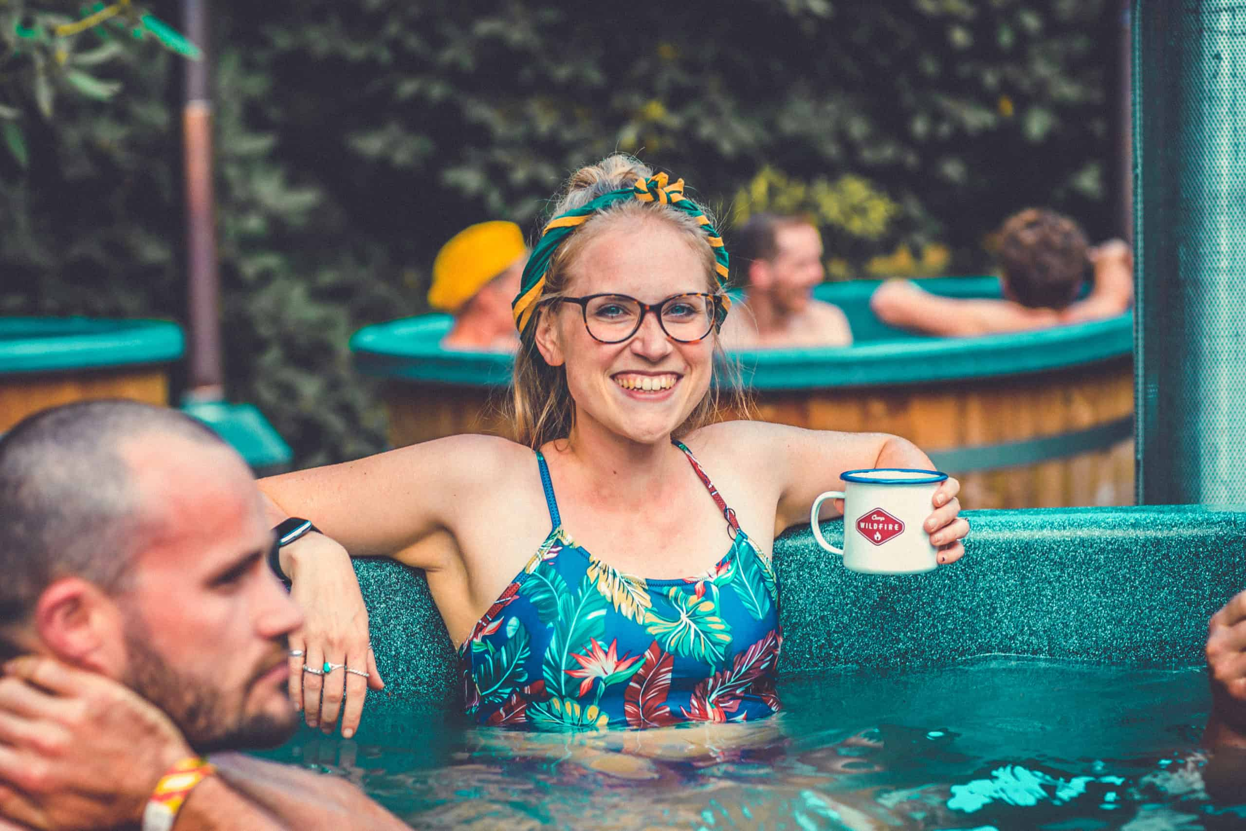 Girl in swimsuit with Camp Wildfire mug sat in the spa. A summer weekend break in a forest near London and Kent. An outdoor woodland retreat featuring adventure activities, live music, DJs, parties and camping. Half summer adventure activity camp, half music festival, for adults only.