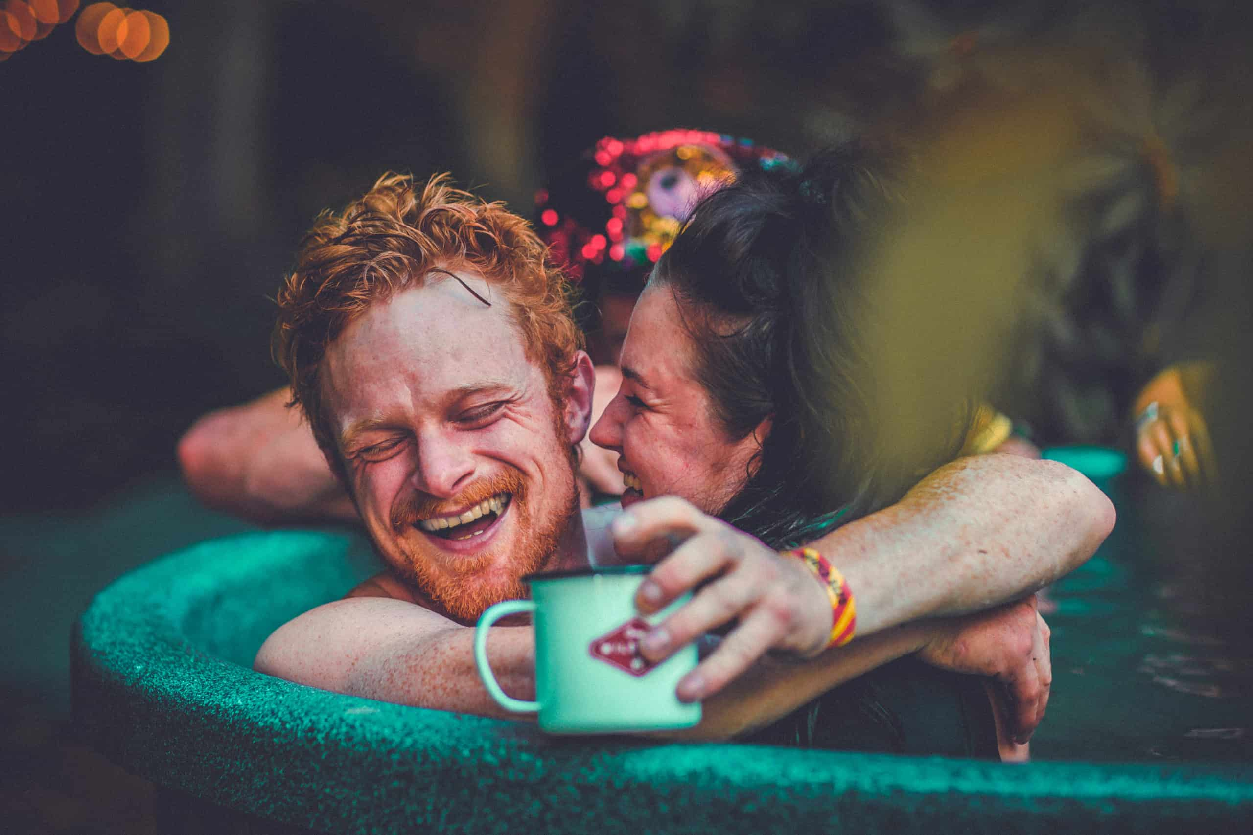 Man and woman embrace in a hot tub, whilst holding a Camp Wildfire mug. A summer weekend break in a forest near London and Kent. An outdoor woodland retreat featuring adventure activities, live music, DJs, parties and camping. Half summer adventure activity camp, half music festival, for adults only