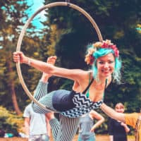 Girl with blue hair hangs from circus hoop. A summer weekend break in a forest near London and Kent. An outdoor woodland retreat featuring adventure activities, live music, DJs, parties and camping. Half summer adventure activity camp, half music festival, for adults only.