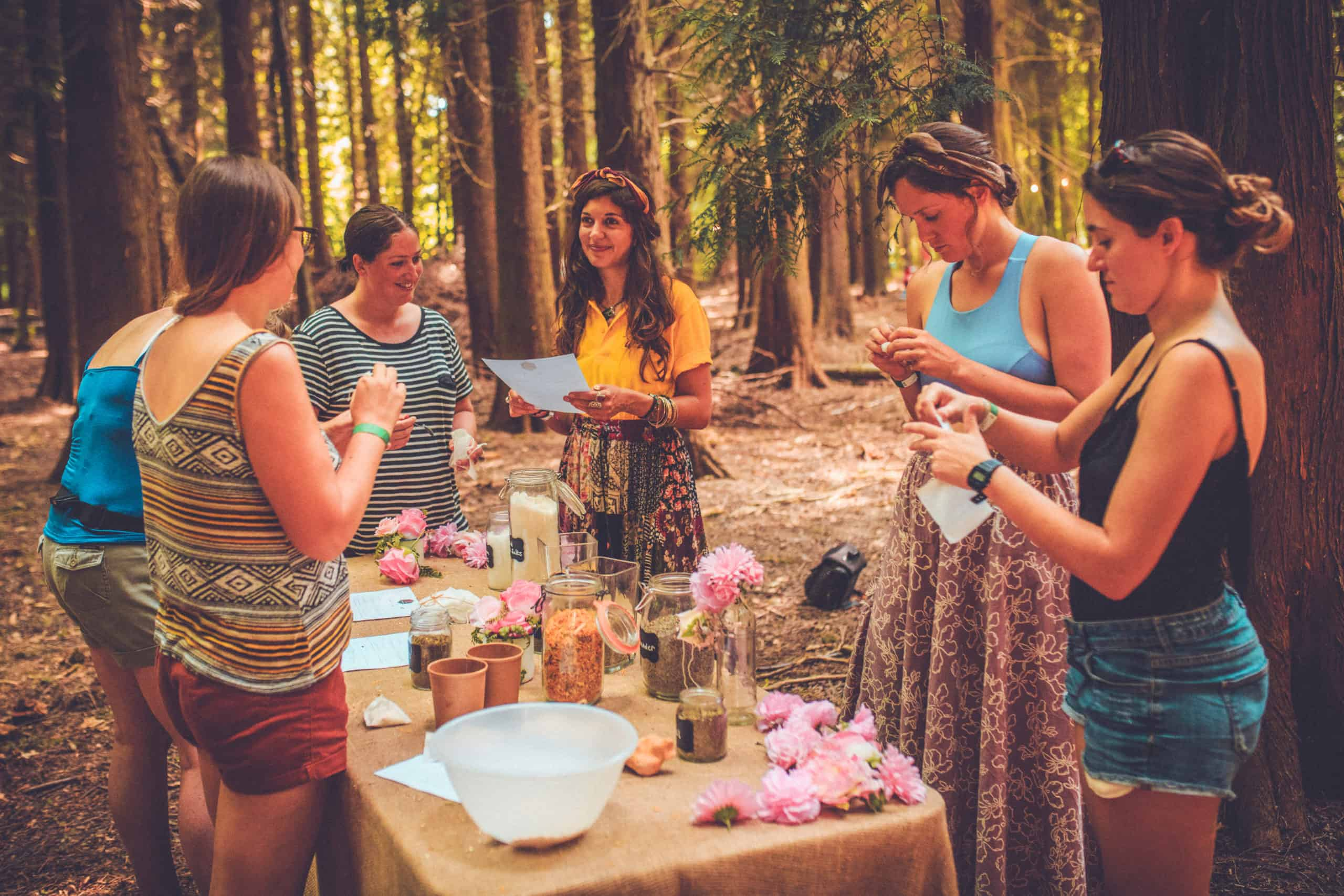 A group mixing ingredients at the Camp Wildfire woodland Apothecary. A summer weekend break in a forest near London and Kent. An outdoor woodland retreat featuring adventure activities, live music, DJs, parties and camping. Half summer adventure activity camp, half music festival, for adults only.