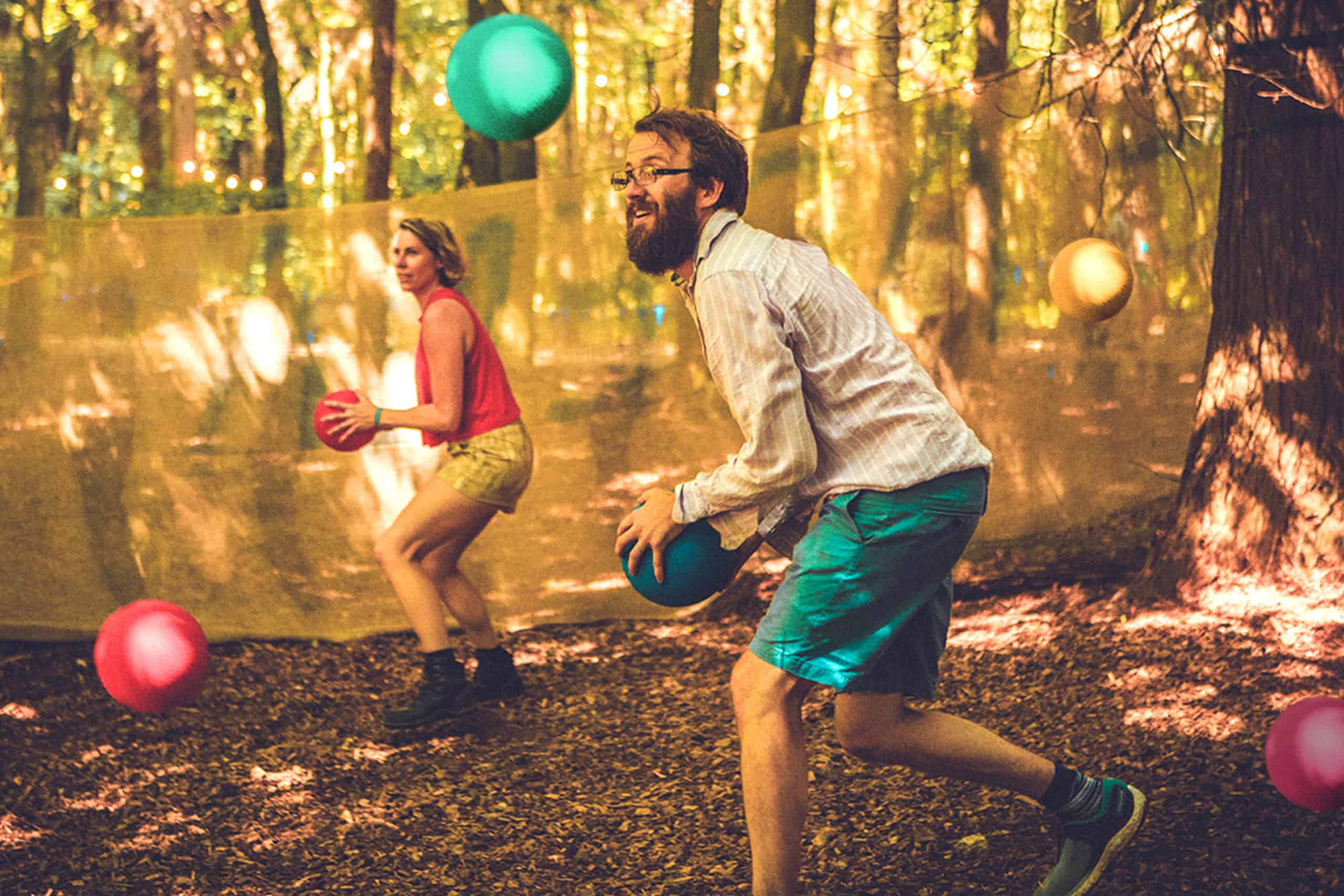 A man and a woman playing dodgeball in the woodland. A summer weekend break in a forest near London and Kent. An outdoor woodland retreat featuring adventure activities, live music, DJs, parties and camping. Half summer adventure activity camp, half music festival, for adults only.