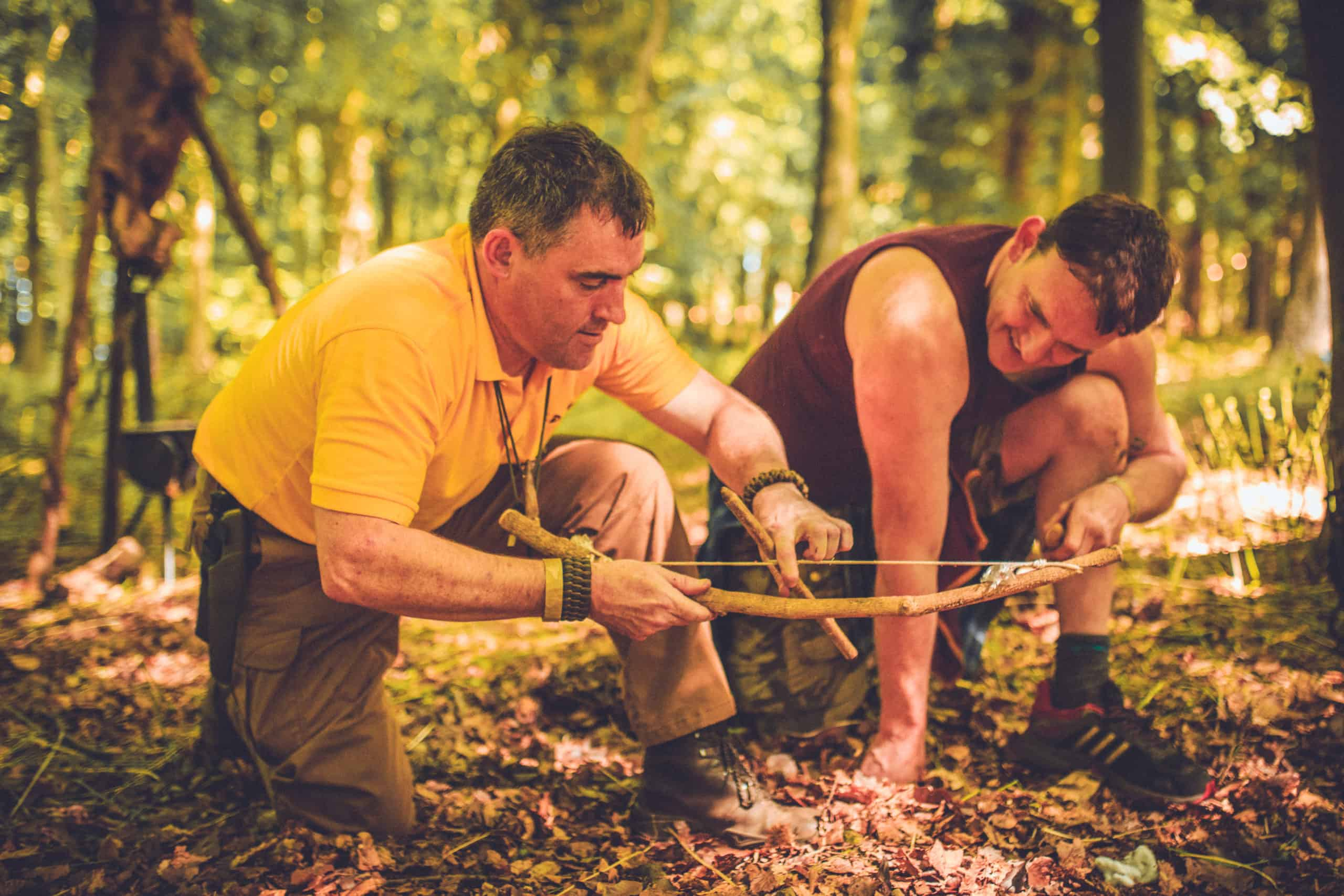 Instructor in yellow shirt showing camper how to make a bow. A summer weekend break in a forest near London and Kent. An outdoor woodland retreat featuring adventure activities, live music, DJs, parties and camping. Half summer adventure activity camp, half music festival, for adults only.