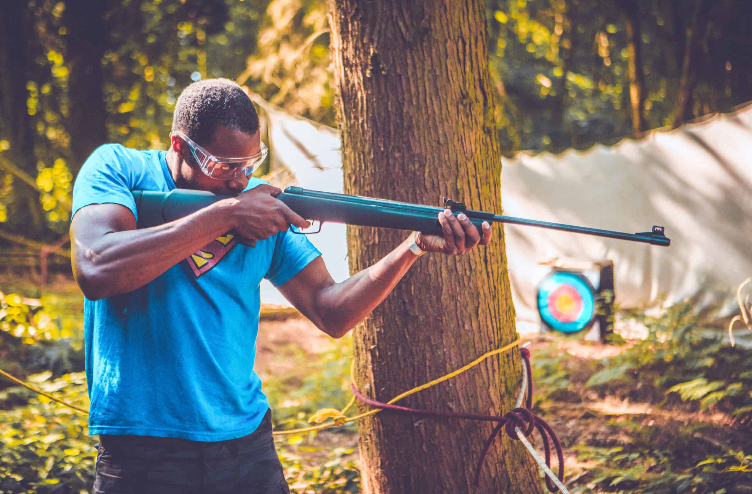 Man at pistol shooting activity at Camp Wildfire. A summer weekend break in a forest near London and Kent. An outdoor woodland retreat featuring adventure activities, live music, DJs, parties and camping. Half summer adventure activity camp, half music festival, for adults only.