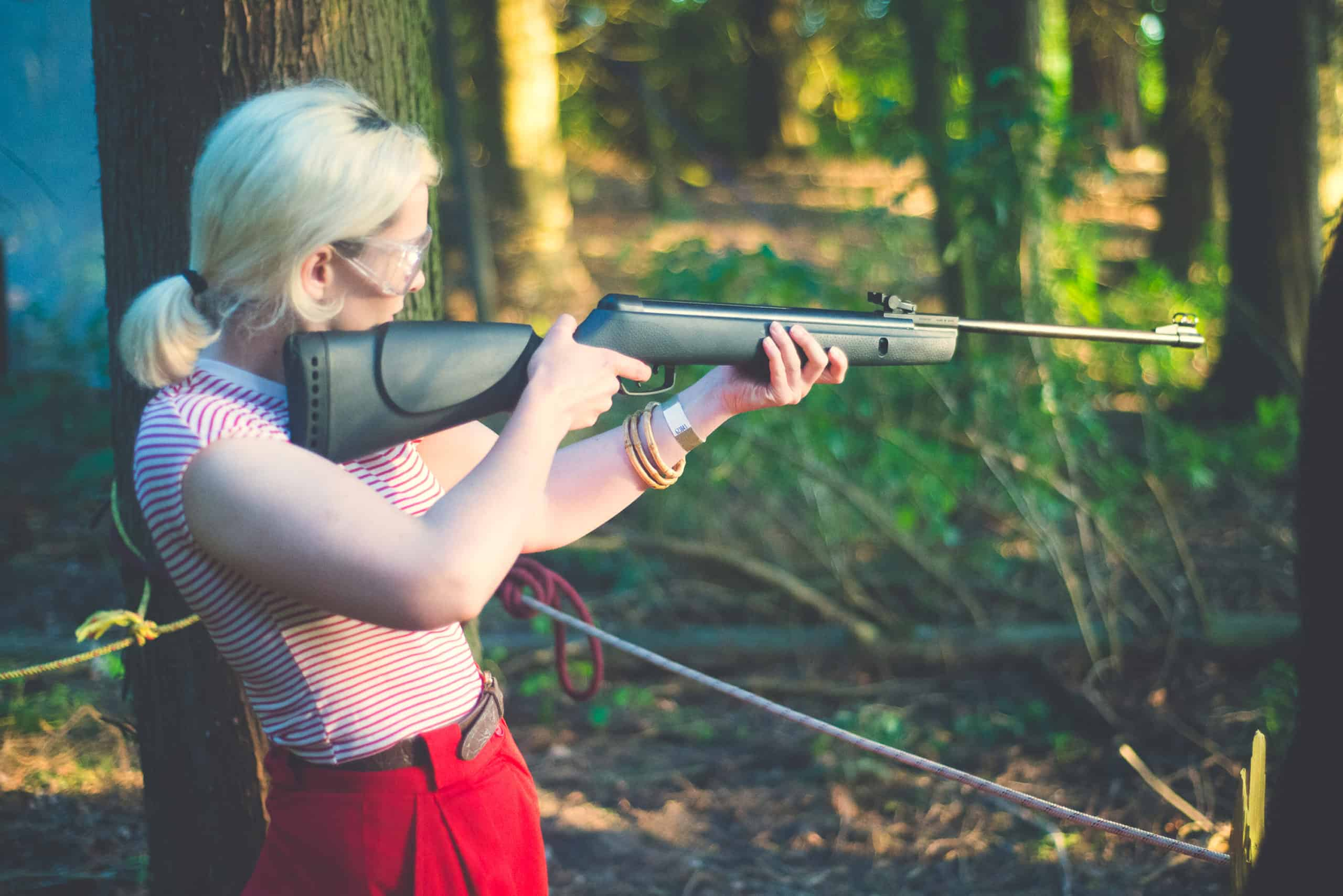 Girl at rifle shooting activity at Camp Wildfire. A summer weekend break in a forest near London and Kent. An outdoor woodland retreat featuring adventure activities, live music, DJs, parties and camping. Half summer adventure activity camp, half music festival, for adults only.
