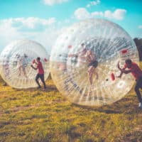 Camp Wildfire zorbing activity. A summer weekend break in a forest near London and Kent. An outdoor woodland retreat featuring adventure activities, live music, DJs, parties and camping. Half summer adventure activity camp, half music festival, for adults only.