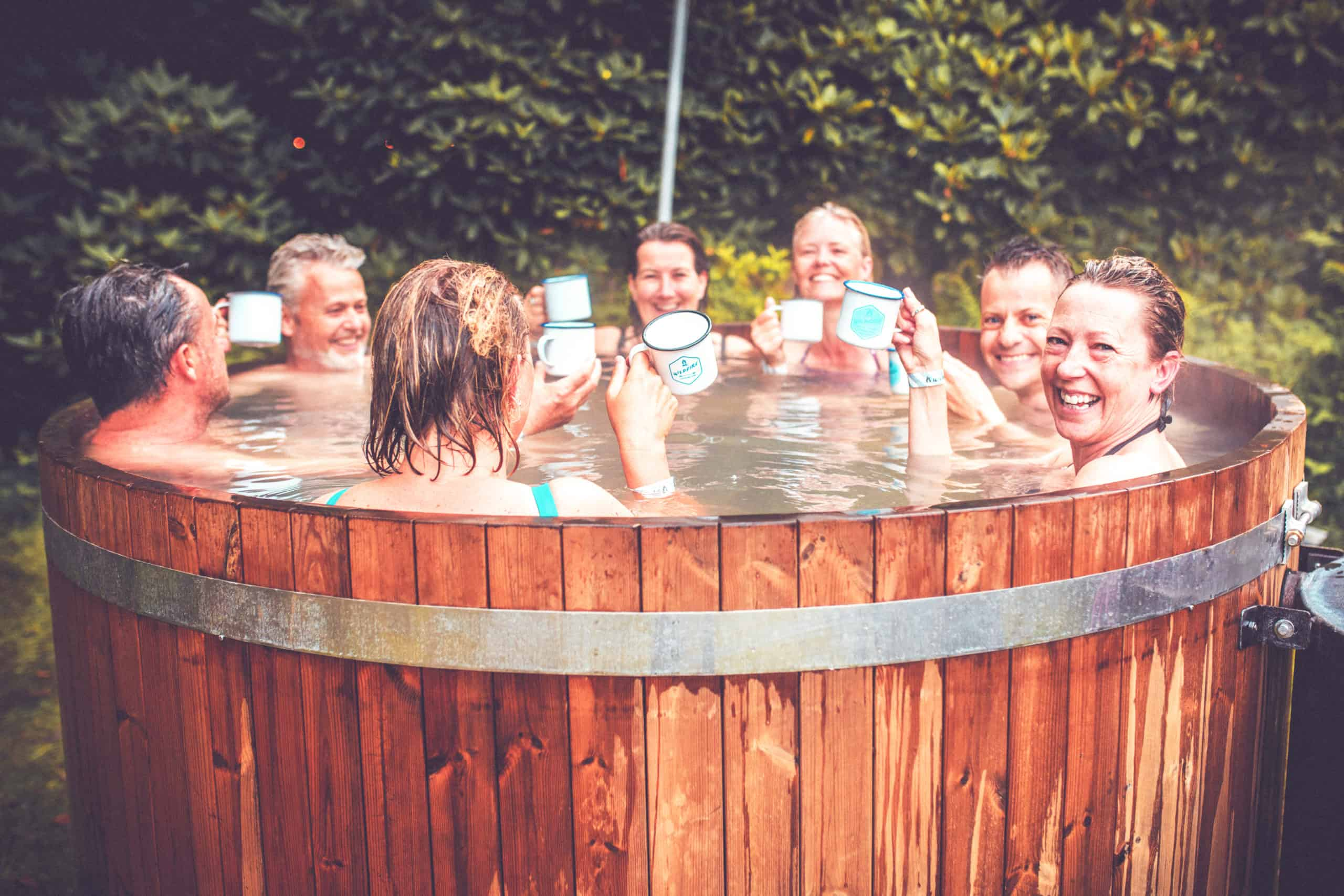 Group of people sat in a hot-tub at the outdoor spa at Camp Wildfire. A summer weekend break in a forest near London and Kent. An outdoor woodland retreat featuring adventure activities, live music, DJs, parties and camping. Half summer adventure activity camp, half music festival, for adults only.