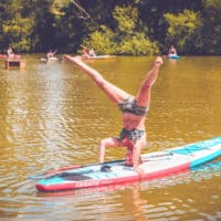 Person doing a headstand at the paddle board activity at Camp Wildfire. A summer weekend break in a forest near London and Kent. An outdoor woodland retreat featuring adventure activities, live music, DJs, parties and camping. Half summer adventure activity camp, half music festival, for adults only.