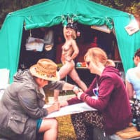 Naked model poses in life drawing session. A summer weekend break in a forest near London and Kent. An outdoor woodland retreat featuring adventure activities, live music, DJs, parties and camping. Half summer adventure activity camp, half music festival, for adults only.