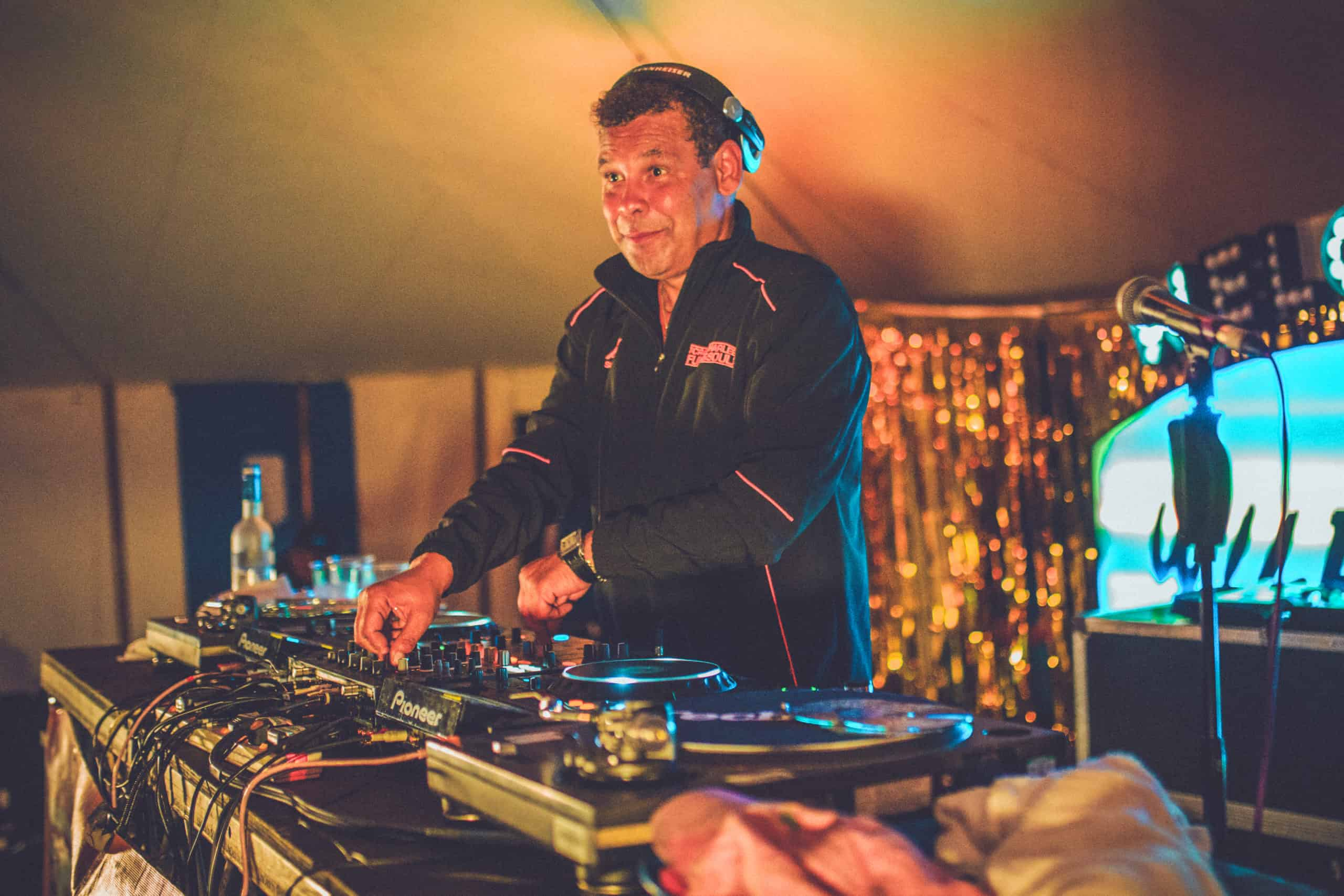 Craig Charles on the decks at Camp Wildfire. A summer weekend break in a forest near London and Kent. An outdoor woodland retreat featuring adventure activities, live music, DJs, parties and camping. Half summer adventure activity camp, half music festival, for adults only.