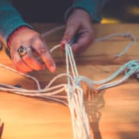 Close up of macrame activity at Camp Wildfire. A summer weekend break in a forest near London and Kent. An outdoor woodland retreat featuring adventure activities, live music, DJs, parties and camping. Half summer adventure activity camp, half music festival, for adults only.