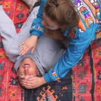 Woman in brightly patterned jacket and glitter on her face performs first aid on a man in a grey hoodie. A summer weekend break in a forest near London and Kent. An outdoor woodland retreat featuring adventure activities, live music, DJs, parties and camping. Half summer adventure activity camp, half music festival, for adults only.