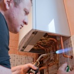 Heating engineer installing a boiler replacement