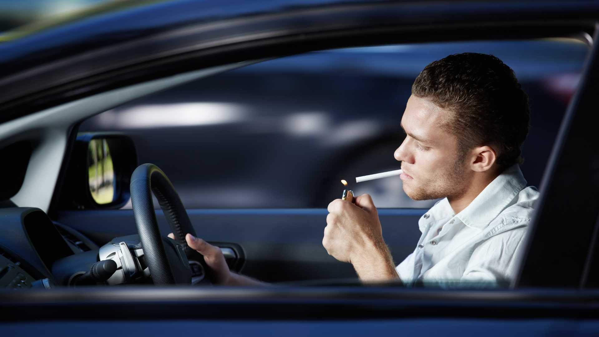 man-lights-cigarette-in-car-while-driving
