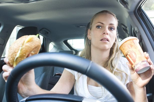 Woman-eating-and-drinking-coffee-while-driving